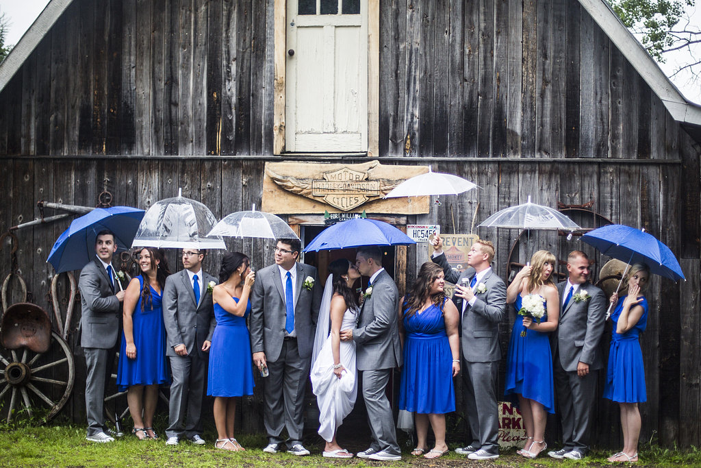 blue umbrellas and wedding party in the rain